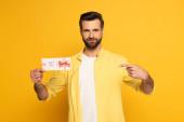 Hezký muž ukazuje prstem na dárkové karty na žlutém pozadí