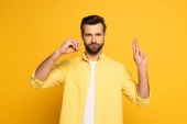 Handsome man showing letters in deaf and dumb language on yellow background
