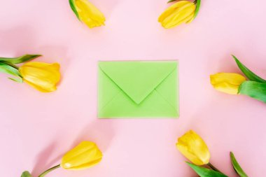 Top view of green envelope near yellow tulips on pink, mothers day concept stock vector