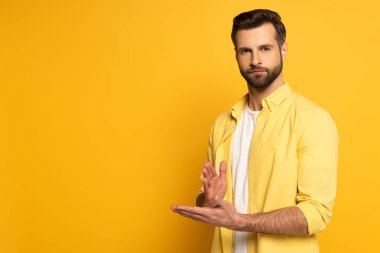 Young man looking at camera while showing gesture in deaf and dumb language on yellow background stock vector
