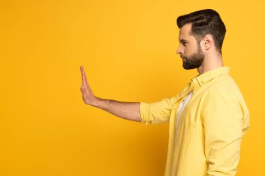 Side view of handsome man showing no sign on yellow background