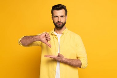 Handsome man showing gesture in deaf and dumb language and looking at camera on yellow background stock vector