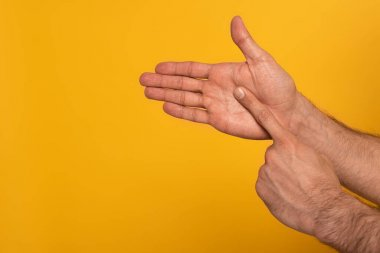 Cropped view of male hands showing gesture in deaf and dumb language isolated on yellow stock vector