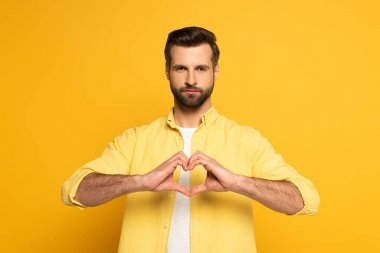 Handsome man showing love sign on yellow background stock vector