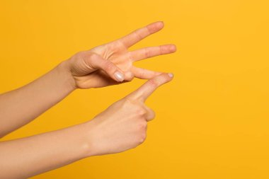 Cropped view of woman gesturing while using sign language isolated on yellow stock vector
