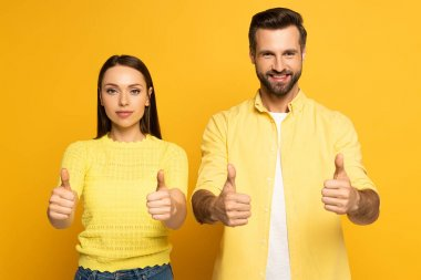 Young couple showing tums up at camera on yellow background stock vector