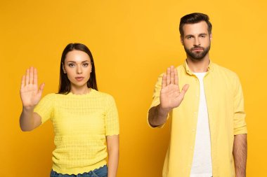 Young couple showing stop gesture at camera on yellow background stock vector