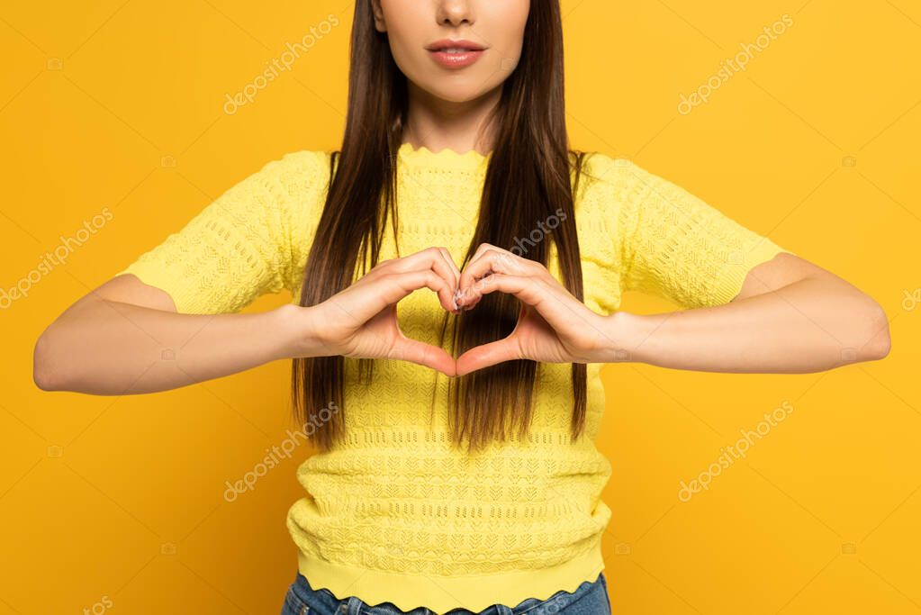 Cropped view of woman showing love sign on yellow background stock vector