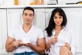Mezirasový pár s podšálky a šálky kávy s úsměvem a při pohledu do kamery v blízkosti kuchyňských skříněk