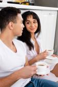 Mezirasový pár s podšálky a šálky kávy s úsměvem a africký Američan dívka při pohledu na muže v blízkosti kuchyňské skříně