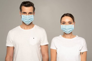 Young couple in medical masks looking at camera isolated on grey stock vector