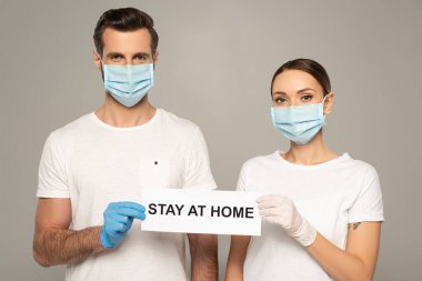 Young couple in medical masks holding card with stay at home lettering isolated on grey stock vector