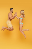 Photo side view of young couple levitating with joined hands on yellow background