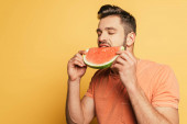 schöner junger Mann mit geschlossenen Augen isst reife, saftige Wassermelone auf gelbem Hintergrund