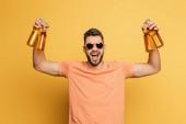 izgatott fiatalember napszemüvegben kezében üveg sört, miközben nézi a kamera sárga háttér