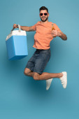 Photo excited man in sunglasses jumping while holding bottle of beer and portable fridge on blue background