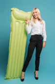 Photo full length view of smiling businesswoman pointing with finger at inflatable mattress on blue background