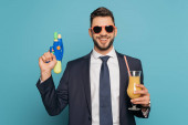 happy businessman holding cocktail glass with orange juice and water gun on blue background