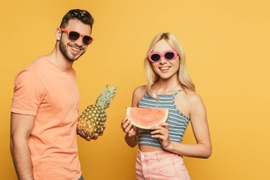 Cheerful man holding whole pineapple near smiling blonde girl with piece of watermelon on yellow background stock vector