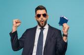 vzrušený podnikatel v slunečních brýlích ukazuje vítězný gesto, zatímco drží pasy a letenky izolované na modré