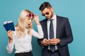 šokovaná podnikatelka držící dokumenty a dotýkající se slunečních brýlí při pohledu na smartphone v rukou podnikatele na modrém pozadí