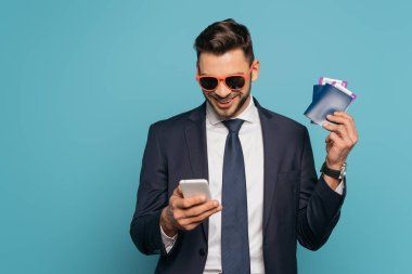 Cheerful businessman in sunglasses chatting on smartphone while holding passports and air tickets isolated on blue stock vector