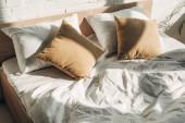postel s polštáři se slunečním světlem a stíny