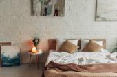 interiér ložnice s postelí, himálajská solná lampa, tulipány a obrazy