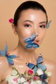 atraktivní něžné nahé asijské dívka v květinách s motýly na obličeji izolované na béžové