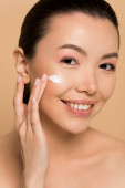 attractive naked asian girl applying cosmetic cream on face isolated on beige