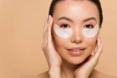 atraktivní něžná asijské žena s kolagen oční podložky izolované na béžové