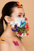 Fotografie attractive asian woman in floral face mask with butterflies isolated on beige