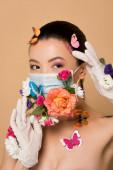 krásná asijská žena v latexové rukavice a květinová maska s motýly na béžové