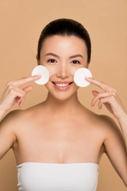 Cheerful asian girl removing makeup from face with cotton pads on beige stock vector