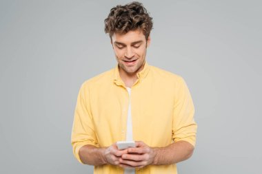 Front view of man smiling and chatting on smartphone isolated on grey stock vector