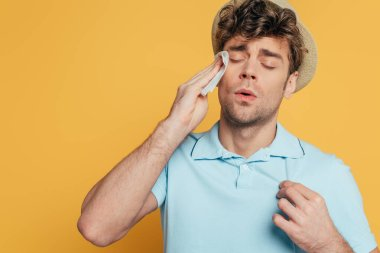 Sweaty man wiping face with napkin isolated on yellow stock vector