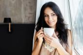 usmívající se mladá žena drží šálek kávy a dívá se oknem