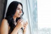 Fotografie atraktivní dívka drží šálek kávy a dívá se oknem