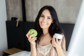 smiling woman holding apple and plastic container with cosmetic cream in bedroom