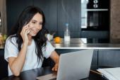 boldog nő beszél az okostelefonon, és dolgozik laptop a konyhában során elszigeteltség