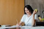šťastná dívka pracuje s obchodními dokumenty a drží jablko doma na vlastní izolaci