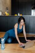 lächelnde schöne Sportlerin sitzt auf Fitnessmatte mit Wasserflasche und Laptop