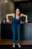 Fotografie šťastný atletický žena školení s činky na fitness podložka