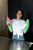 usmívající se žena v latexových rukavicích čistící stůl s růžovým hadrem