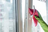 Ausgeschnittene Ansicht einer Frau in Gummihandschuhen, die Fenstergriff mit rosa Lappen putzt