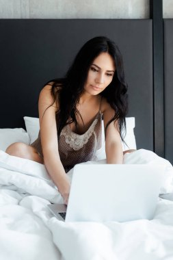 Attractive young woman using laptop in bed on self isolation stock vector