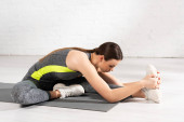 young and flexible sportswoman warming up on fitness mat