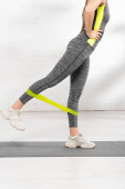 Fotografie cropped view of sportive girl with hand on hip exercising with resistance band on fitness mat