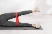 ostříhaný pohled na sportovně cvičenou ženu s páskou odporu na fitness podložce