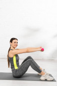 Photo cheerful young sportswoman exercising with pink dumbbells on fitness mat